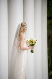 Natural bride among columns Stock Image