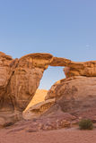 Natural Bridge with moon in Wadi Rum, Jordan Stock Photo
