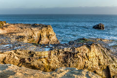 Sunlit Rocks at Natural Bridges State Beach Royalty Free Stock Image