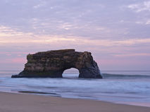 Natural Bridges At Sunrise. Pacific Ocean rock formation at sunrise Stock Images