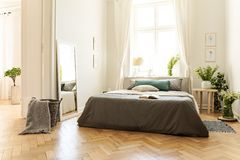 A natural bright apartment interior with wooden floor, white walls and sunny windows. A bed with gray linen and fresh meadow flowe. Rs in the bedroom. Real photo stock images