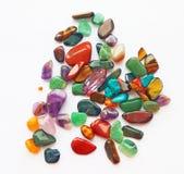 Natural bright coloured semi precious gemstones and gems. Assorted natural bright coloured semi precious gemstones and gems on white background for design and stock image