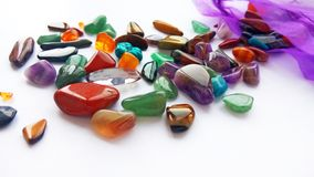 Natural bright coloured semi precious gemstones and gems on white background. Assorted natural bright coloured semi precious gemstones and gems on white stock images