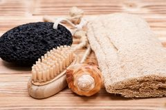 Natural bristle hand and nail wooden brush, volcanic pumice stone, loofah sponge and shell. On wooden vintage background Royalty Free Stock Image