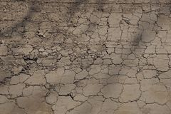 Natural brown texture of dry earth with cracks on the road. Natural brown background from a dry land with cracks on the road royalty free stock photography