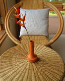 Natural brown color rattan armchair and round table with flower vase by the window Royalty Free Stock Photo