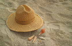 Natural brown color straw hat with many types of little seashells scattered on the sandy beach Stock Image