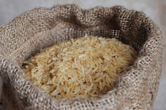 Natural brown rice. In small burlap sack royalty free stock images
