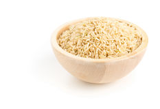 Natural brown uncooked rice in wooden bowl. Over white background royalty free stock images