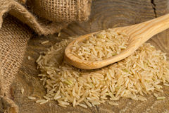 Natural brown uncooked rice on wooden spoon Royalty Free Stock Images