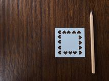 Natural brown wood pencil and white square blank paper which was punched in heart shape Royalty Free Stock Photos