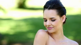 Natural brunette smiling at camera in the park stock video