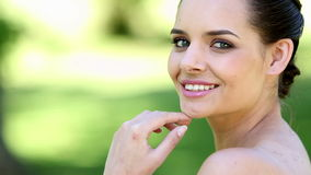 Natural brunette smiling at camera in the park stock video footage