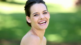 Natural brunette smiling at camera in the park stock footage
