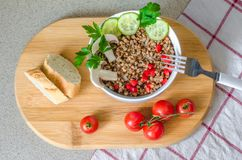 Natural buckwheat porridge with chopped sweet red pepper and parsley. Natural buckwheat porridge with chopped sweet red pepper, parsley, sliced cucumber and Royalty Free Stock Photo