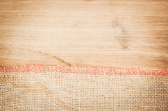 Natural burlap and natural tinted wood surface Stock Photography