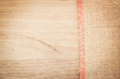 Natural burlap and natural tinted wood surface Royalty Free Stock Images
