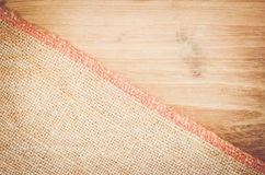 Natural burlap and natural tinted wood surface Stock Image