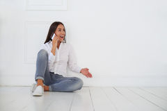Natural burst of lovely positive emotions. An attractive brunette has rather lively conversation on her smart phone while sitting on the floor royalty free stock photography