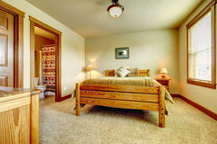 Natural cabin farm house bedroom with beige carpet and green walls. Royalty Free Stock Photos
