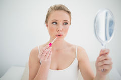 Natural calm blonde holding mirror and applying lip gloss Stock Images