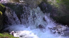 Natural cascade runs between large stones covered with green moss and makes splashes fresh and pure water and foam in. Slow motion close-up stock video