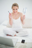 Natural cheerful blonde holding mirror and mascara Royalty Free Stock Photo