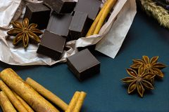 Natural chocolate with lavender flowers cinnamon and star anise on a dark background. Chocolate with lavender flowers cinnamon and star anise on a dark royalty free stock images
