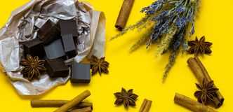 Natural chocolate with lavender flowers, cinnamon and star anise over yellow background. Chocolate with lavender flowers, cinnamon and star anise over yellow stock image