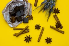 Natural chocolate with lavender flowers, cinnamon and star anise over yellow background. Chocolate with lavender flowers, cinnamon and star anise over yellow royalty free stock image