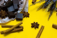 Natural chocolate with lavender flowers, cinnamon and star anise over yellow background. Chocolate with lavender flowers, cinnamon and star anise over yellow stock photos