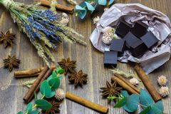 Natural chocolate with lavender flowers cinnamon and star anise on a wooden background. Chocolate with lavender flowers cinnamon and star anise on a wooden royalty free stock image
