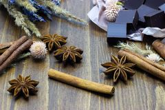 Natural chocolate with lavender flowers cinnamon and star anise on a wooden background. Chocolate with lavender flowers cinnamon and star anise on a wooden stock photo
