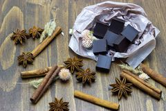 Natural chocolate with lavender flowers cinnamon and star anise on a wooden background. Chocolate with lavender flowers cinnamon and star anise on a wooden royalty free stock photos
