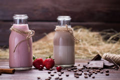 Natural chocolate and strawberry milkshakes. Chocolate, coffee beans and berries on a wooden background stock images