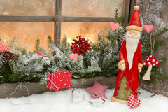 Natural christmas decoration with santa claus in a wooden window. With snow - in red and white for a greeting card Stock Images