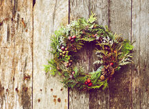 Natural Christmas wreath. Richly toned vintage style image image of a home made christmas wreath with natural decorations hanging on a rustic wooden wall with stock photos