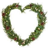 Natural Christmas Wreath. Christmas heart shaped floral wreath with mistletoe, ivy, fir and pine cones over white background royalty free stock photos