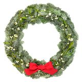 Natural Christmas Wreath. Christmas and winter natural wreath with snow covered spruce fir and mistletoe with red bow on white background royalty free stock photography