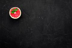 Natural citrus cosmetics. Spa salt near grapefruit on black background top view mockup. Natural citrus cosmetics. Spa salt near fresh grapefruit on black royalty free stock photography