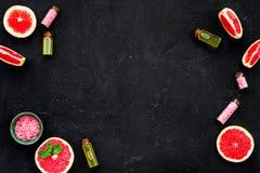 Natural citrus cosmetics. Spa salt near grapefruit on black background top view mockup. Natural citrus cosmetics. Spa salt near fresh grapefruit on black stock photo