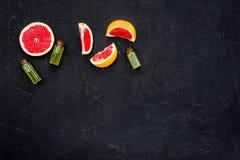 Natural citrus cosmetics. Spa salt near grapefruit on black background top view mockup. Natural citrus cosmetics. Spa salt near fresh grapefruit on black royalty free stock image