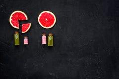 Natural citrus cosmetics. Spa salt near grapefruit on black background top view mockup. Natural citrus cosmetics. Spa salt near fresh grapefruit on black stock image
