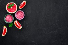 Natural citrus cosmetics. Spa salt near grapefruit on black background top view mockup. Natural citrus cosmetics. Spa salt near fresh grapefruit on black stock photos