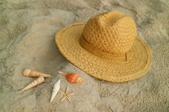 Natural color straw hat on the sand beach with many types of little seashells Royalty Free Stock Images