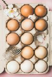 Natural colored eggs in box for Easter. Easter holiday background. Flat-lay of gradient natural colored eggs in box with tender Spring almond blossom flower and Royalty Free Stock Photography