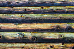 Natural colorful weathered log cabin wood wall. Wooden background pattern. Natural colors on old weathered log cabin wood wall. Wall texture background pattern Stock Images