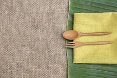 Natural concept kitchen, wooden fork and spoon on yellow napkin on green banana leaf. And hessian fabric background, natural concept kitchen royalty free stock photos