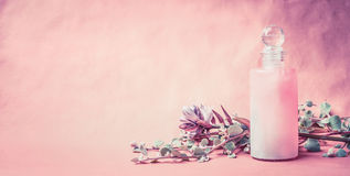 Natural cosmetic product in bottle with herbs and flowers on pink background, front view, banner, place for text. Healthy skin or Stock Photo