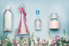 Natural cosmetic products. Jars and bottles with tonic , mist, perfume,cream ,tonic and micellar water on herbal leaves and wild f stock image
